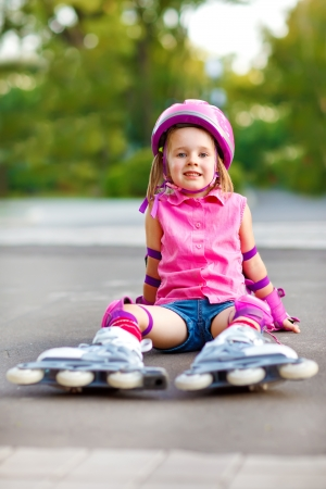 Attractive smiling child in roller skates and protective equipment