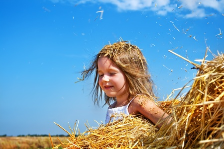 closed eyes: Portret van een gelukkig meisje met gesloten ogen, zittend in een hooiberg