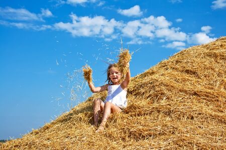 Happy kid sitting in a haystack Stock Photo - 14814557