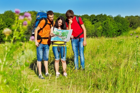 Three teenagers with backpacks looking at the tour map Stock Photo - 14856831