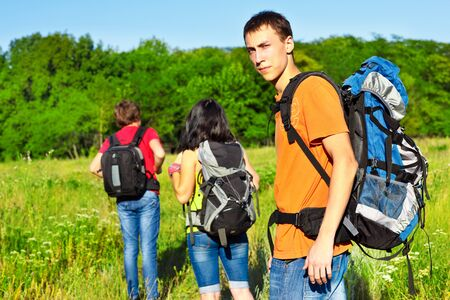 Active young friends with backpacks hiking Stock Photo - 15199179