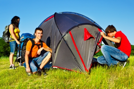 Three teenage backpackers beside camping tent