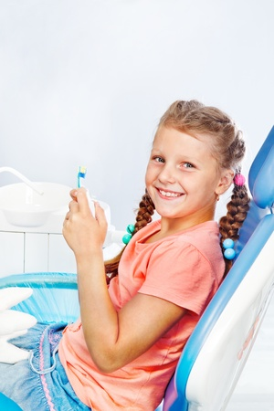 Cheerful kid with toothbrush and toothpaste at the dental clinic photo