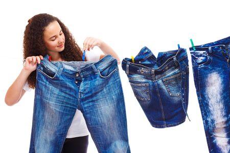 denim skirt: Girl hanging up denim clothing for drying Stock Photo