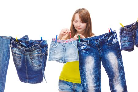 clothes pegs: Teenage girl hanging up denim clothing for drying Stock Photo