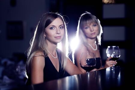Two stylish female friends sit with wine glasses photo