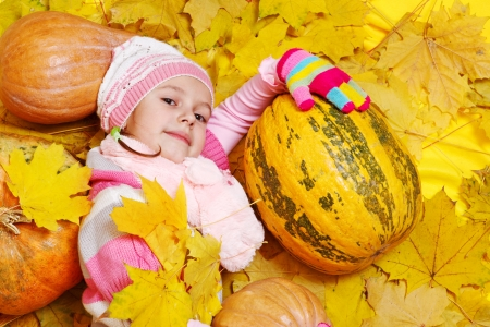 Girl with pumpkins lying on autumnal  leaves photo