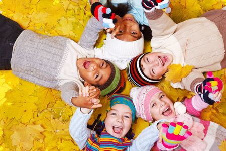 Joyful kids lie on yellow leaves