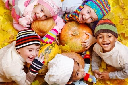 enfants qui rient: Groupe de gosses sur les feuilles jaunes et des citrouilles