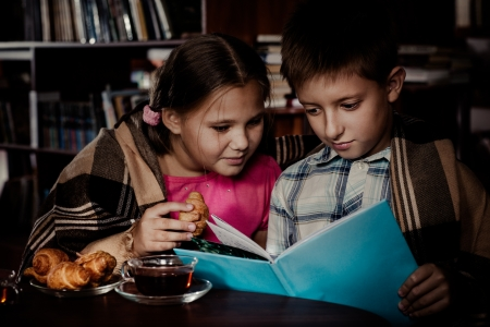 Two kids reading book in a dark library photo