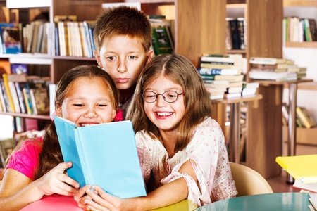 school aged: Kids reading book in a school library Stock Photo