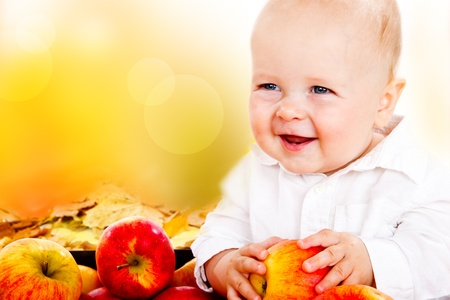 Portrait of a cheerful baby holding apples in hands