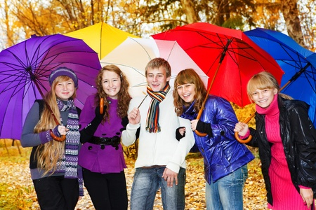 Teenage friends with umbrellas in a park photo