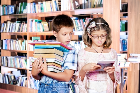 Boy with books pile and girl with e-reader Stock Photo