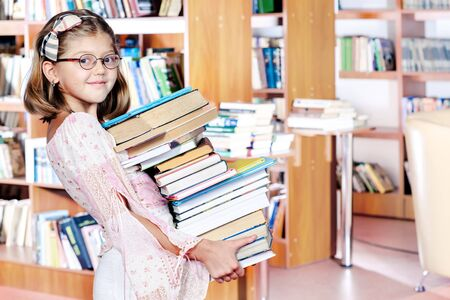 Girl holding the books pile photo