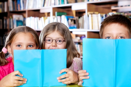 Pleased children hide behind books photo
