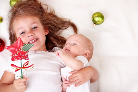 naptime: Elder sister and newborn baby playing with  Christmas star Stock Photo