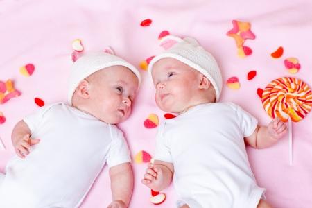niñas gemelas: Bebés gemelos recién nacidos que mienten entre dulces Foto de archivo