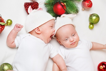 Emotional Christmas twin babies in white clothing photo