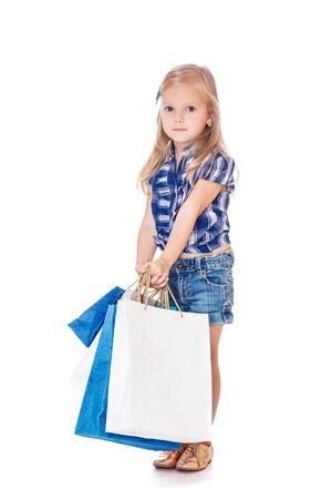 Blond little shopper in denim wear with shopping bags photo