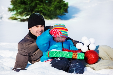 Dad and son with Christmas present and decoration, lying in snow photo