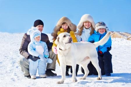 animal winter: White winter labrador dog and family beside him