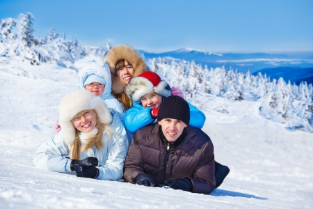Cheerful parents and three kids lie on snow