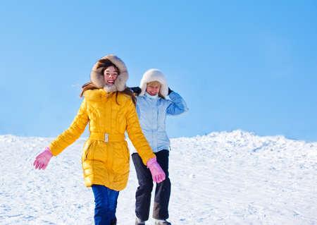 madre e hija adolescente: Corriendo por la colina nevada