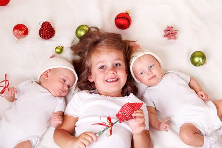 Siblings with Christmas decoration lie on bed photo