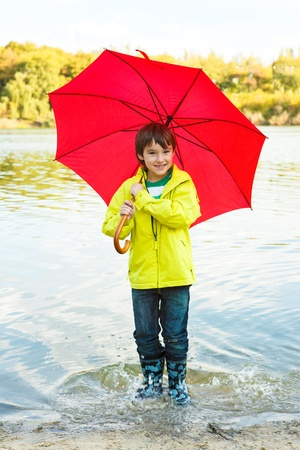 Joyful boy with umbrella hopping in water photo