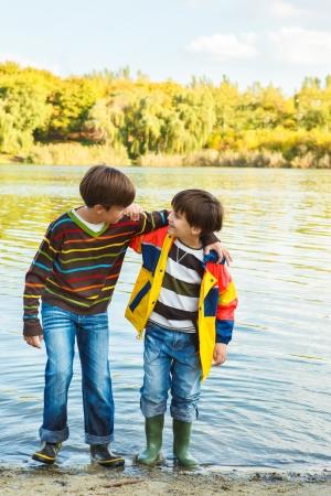botas de lluvia: Hermanos que abrazan en parque del oto�o