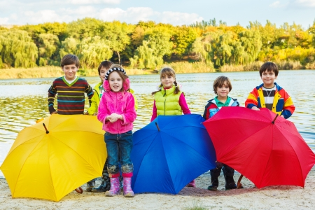 Kids in rubber boots stand on the autumn beach behind umbrellas photo