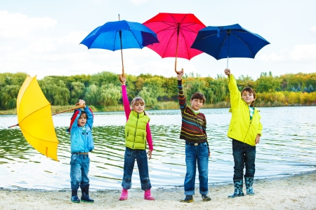 Kids in autumn clothing holding colorful umbrellas photo