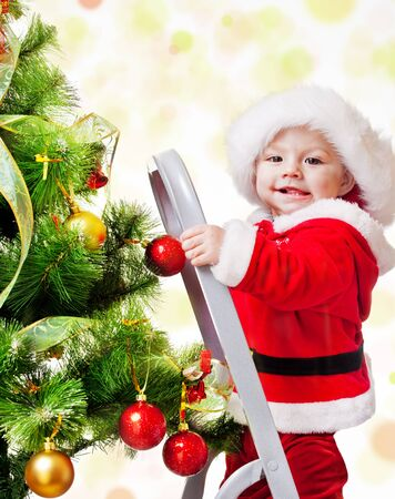decorating christmas tree: Happy Christmas baby standing on a step ladder decorating Xmas tree