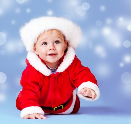 Crawling sweet Santa helper over blue snowy background photo