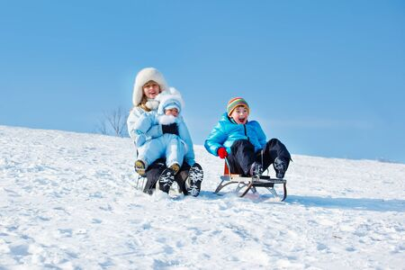 Active mother and kids sleighing down the snowy hill photo