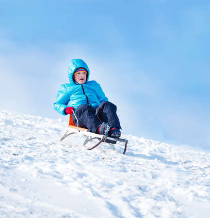 Winter sleighing activity - boy riding down the hill photo