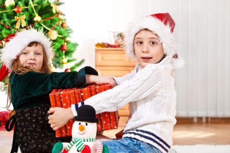 family fight: Kids in Santa hat holding one Christmas present box Stock Photo