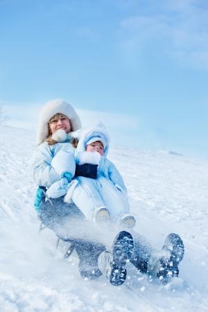 trineo: Madre alegre y su hijo pequeño deslizamiento hacia abajo de la colina del invierno