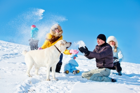 ropa de invierno: Los ni�os y los padres que lanzan nieve en una colina invierno Foto de archivo