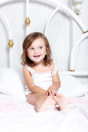 Sweet barefoot toddler girl in bed Stock Photo