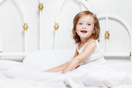 Beautiful laughing toddler girl sits in bed photo