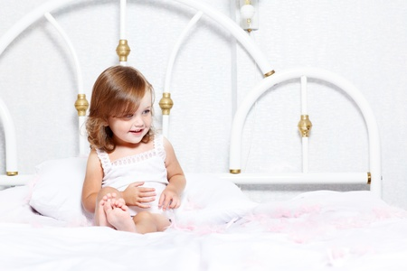 Smiley little girl playing with feathers in bed photo