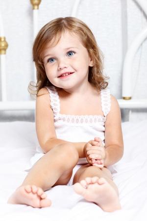 jolie petite fille: Douce fille réfléchie peu assis dans son lit