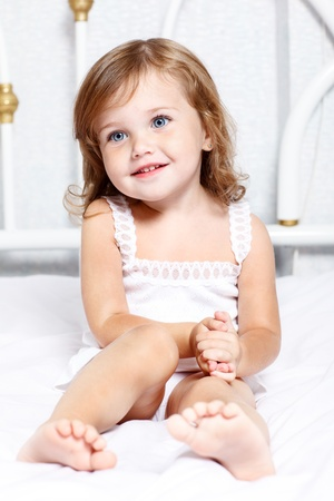 cute little girl smiling: Sweet thoughtful little girl sits in bed