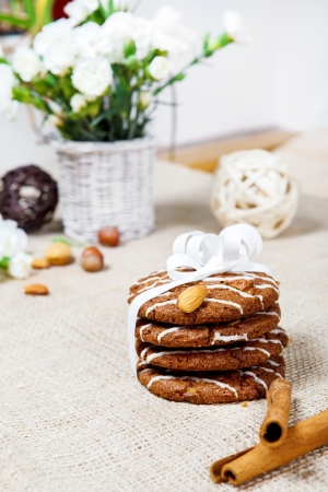 Cinnamon sticks and cookies pile lying on burlap photo