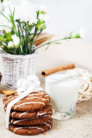 Natural homemade cookies wrapped in white ribbon, milk and flowers for someone special photo