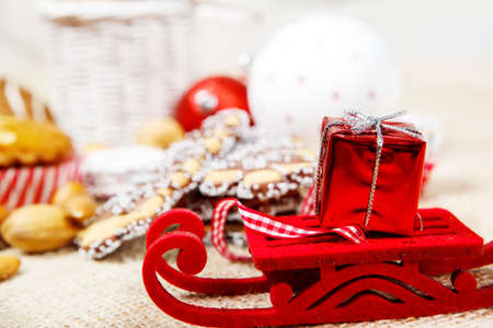 Small Christmas sleigh with tiny present box on Stock Photo - 16256376