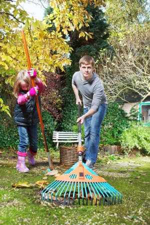 Father and daughter raking autumn leaves in the backyard photo