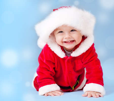 Sweet baby wearing Santa costume, over blue background with copyspace photo